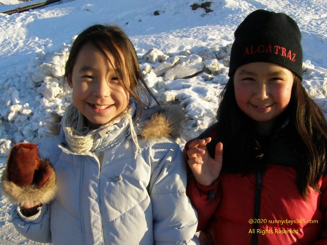 カメラに向かって笑顔を見せるイヌイットの女の子たち