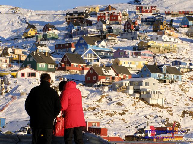 カコルトクに降り立った夫婦の後ろ姿と北極圏ならではのカラフルな街並み