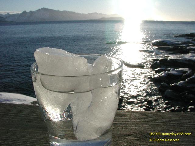 北極圏の海に降り注ぐ太陽とロックグラス