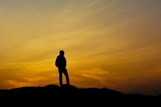 夕陽の中で明日を見つめる男