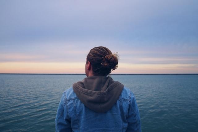 大海原を見つめ考えている女性の後ろ姿