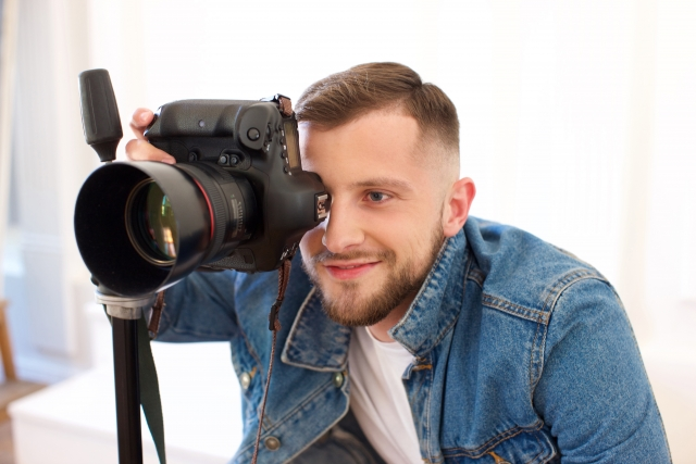 両目を開いてカメラを覗くカメラマン