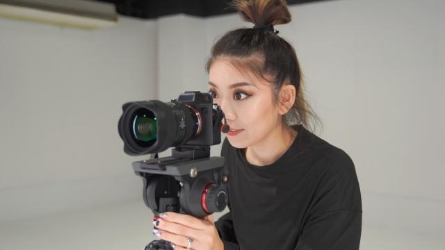 両目を開いて撮影する女性カメラマン