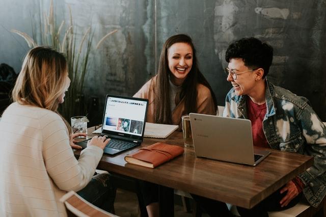 男女3人がパソコンを囲んで楽しく会話している