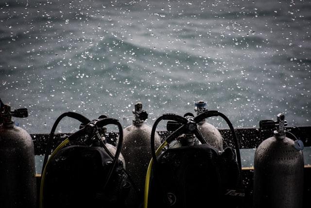 悪天候の中に並べられたダイビング用空気ボンベ
